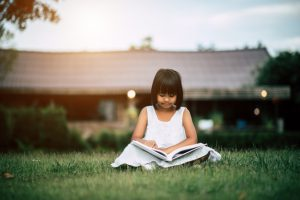 little-girl-reading-a-book-in-the-house-garden_1150-4081